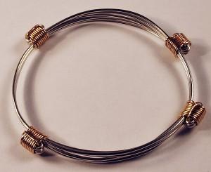 Slender silver bracelet with 4 gold knots