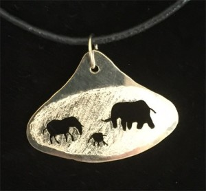 Elephant figures in african hut shaped gold pendant