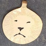 Lion face in round gold pendant